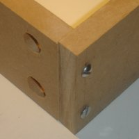 Two pieces of wood joined at a right angle using screws and dross dowels (barrel nuts).